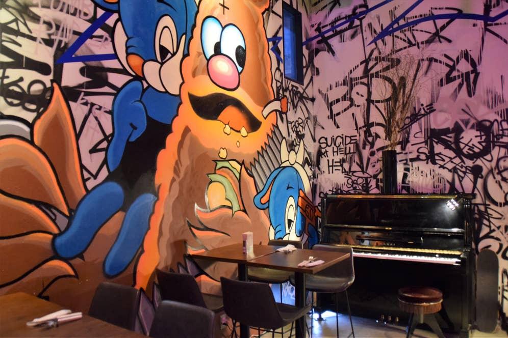 ポップなイラストとアップライトピアノのギャップもおもしろい。店内にはDJブースも。