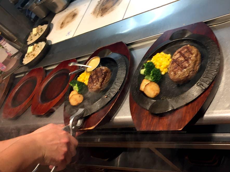 ▲ハンバーグが焼けたら熱々の鉄板ごと木製の皿に乗せる