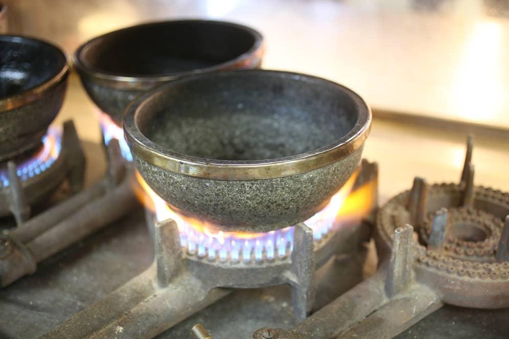 出番を待ついくつもの石鍋がガスコンロの上に載せられ、アクセル全開の炎で炙られている!