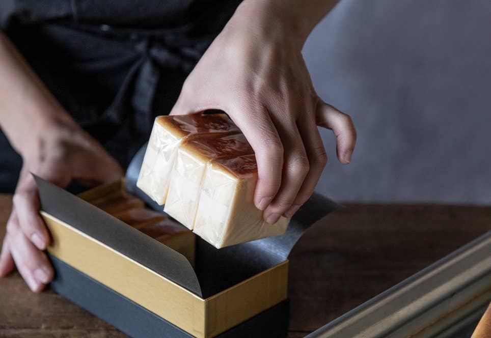 繊細な食感が生命のチーズテリーヌの箱詰めは、一つひとつ手作業で行う。